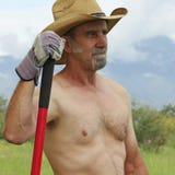 Ein hemdloser Cowboy Pauses While Working auf der Ranch Stockbild