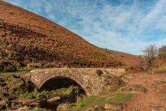 Ein herbstlicher Wasserfall und Steineine packpferdbrücke bei drei Grafschaften stockfoto