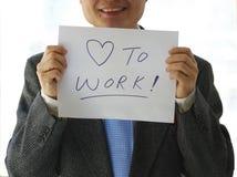 Ein Herr, der eine Karte sagt Liebe, um zu arbeiten anhält Lizenzfreies Stockbild