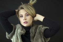 Ein herrliches blondes Modell mit blauen Augen und schwarzer Rollkragen und Pelz bekleiden im Studio Lizenzfreie Stockfotos