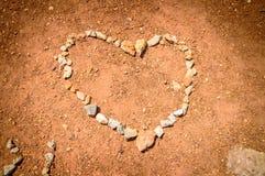 Ein Herz, das von den Steinen auf der roten Erde gemacht wurde, rieb mit einem künstlerischen Lizenzfreie Stockbilder
