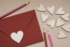 Ein Herz geformtes Valentine& x27; s-Tageskarte in einem roten Umschlag, umgeben durch hölzerne Herzen und farbige Bleistifte Stockfotografie