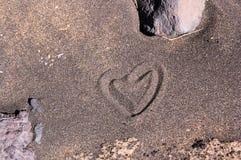 Ein Herz gezeichnet in den schwarzen Sand auf dem Strand lizenzfreie stockbilder