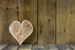 Ein Herz Holz auf einem alten rustikalen Hintergrund für eine Grußkarte. Lizenzfreies Stockfoto