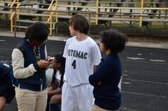 Ein High School Fußballspieler erhält durch einen Reporter für die Schulzeitung gefragt lizenzfreie stockfotografie