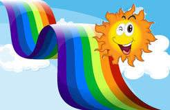 Ein Himmel mit einem Regenbogen und einer glücklichen Sonne Stockfotografie