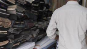 Ein hindischer Schneider nimmt ein Hemd geht zu einer Nähmaschine in einer Werkstatt stock footage