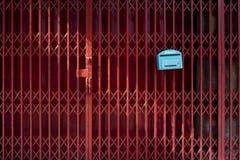 Ein Hintergrund maserte Bild der Rotfensterladentür Stockbild