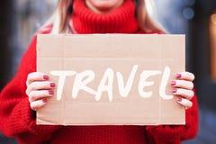 Ein Hippie-Mädchen in einer roten Strickjacke hält eine Papptablette mit Reise der Aufschrift ' stockbilder