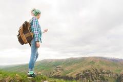 Ein Hippie-Mädchen reiste durch einen Blogger in einem karierten Hemd und mit dem mehrfarbigen Haar unter Verwendung eines Kompas Lizenzfreies Stockfoto