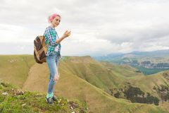 Ein Hippie-Mädchen reiste durch einen Blogger in einem karierten Hemd und mit dem mehrfarbigen Haar unter Verwendung eines Kompas Lizenzfreie Stockfotografie