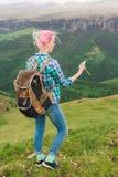 Ein Hippie-Mädchen reiste durch einen Blogger in einem karierten Hemd und mit dem mehrfarbigen Haar unter Verwendung eines Kompas Stockfotos