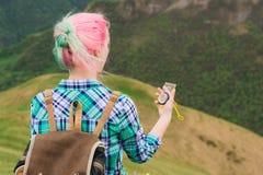 Ein Hippie-Mädchen reiste mit einem Blogger in einem karierten Hemd und mit dem mehrfarbigen Haar unter Verwendung eines Kompasss Lizenzfreie Stockfotografie