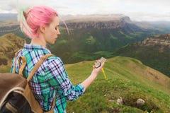 Ein Hippie-Mädchen reiste mit einem Blogger in einem karierten Hemd und mit dem mehrfarbigen Haar unter Verwendung eines Kompasss Stockbilder