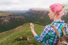 Ein Hippie-Mädchen reiste mit einem Blogger in einem karierten Hemd und mit dem mehrfarbigen Haar unter Verwendung eines Kompasss Stockfotos