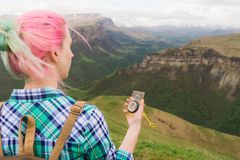 Ein Hippie-Mädchen reiste mit einem Blogger in einem karierten Hemd und mit dem mehrfarbigen Haar unter Verwendung eines Kompasss Stockbild
