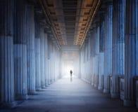Ein historisches Gebäude und ein Mann, die in das Licht gehen Stockbilder