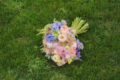 Ein Hochzeitsblumenstrauß auf dem Gras lizenzfreie stockfotos