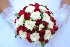 Ein Hochzeitsblumenstrauß von Rosen in den Händen einer Nahaufnahmebraut Lizenzfreie Stockfotografie