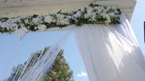 Ein Hochzeitsbogen verziert mit Blumen und großen Wind-entwickelnden Geweben Schießen in der Bewegung stock footage