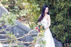 Ein Hochzeitsfoto/-porträt der jungen Frau sitzen auf einer alten alten Brücke in Shanghai-shui BO-parkpark des Wassers Stockbilder