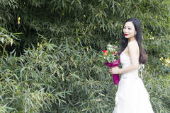 Ein Hochzeitsfoto/-porträt der jungen Frau stehen Bambus in Shanghai-shui BO-parkpark des Wassers bereit Stockfotos