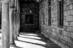 Ein Hofkorridor im Freien in Schwarzweiss mit Säulen und Stein und Fenster Stockfotografie