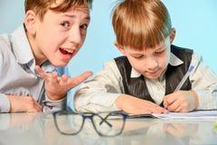 Ein hoher Schüler bereitet einen ersten Sortierer beim dem Schreiben und Vorbereiten für Schule vor Älterer Bruder unterrichtet j stockfotos