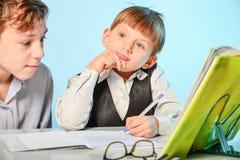 Ein hoher Schüler bereitet einen ersten Sortierer beim dem Schreiben und Vorbereiten für Schule vor Älterer Bruder unterrichtet j stockbilder