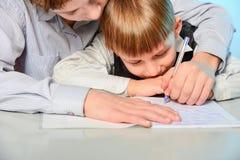 Ein hoher Schüler bereitet einen ersten Sortierer beim dem Schreiben und Vorbereiten für Schule vor Älterer Bruder unterrichtet j lizenzfreie stockfotografie