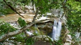 Ein hoher Wasserfall fällt von einer Klippe in einen klaren See stockbild