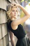Ein hohes blondes mit ihrer Hand im Haar mit einem schwarzen ledernen Kleid Lizenzfreies Stockfoto