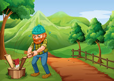 Ein Holzfäller, der das Holz an der Bahn geht zum Bauernhof hackt Stockfoto