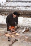 Ein Holzfäller, der einen Klotz mit einer Kettensäge trimmt Lizenzfreie Stockfotos