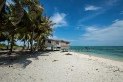 Ein Holzhaus, das den Ozean mit blauem Himmel im Hintergrund gegenüberstellt lizenzfreie stockbilder