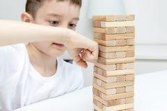 Ein Holzklotz-Turmspiel des jugendlichen kaukasischen Jungen lochendes mit seinem Arm stockfoto