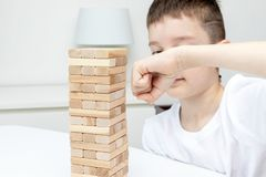 Ein Holzklotz-Turmspiel des jugendlichen kaukasischen Jungen lochendes mit seinem Arm stockbild