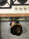 Ein hungriger Junge, der nahe bei dem Ofen in der Küche sitzt stockfotografie