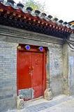 Ein Hutong-Haus-Eingang mit rotem Tor und Grey Colour Brick Wall stockfotografie