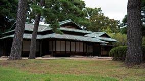 Ein im altem Stil japanisches Haus sitzt in einem klassischen Garten der japanischen Art lizenzfreie stockfotografie