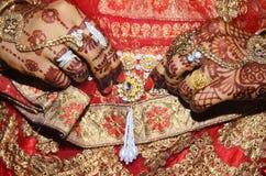 Ein indischer Bräutigam, der ihren goldenen Bauchgurt befestigt wurde über Saree verbrauchter Nahaufnahme zeigt, schoss stockfotografie