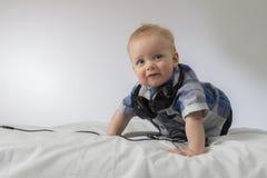 Ein infnat Junge mit Kopfhörern auf seinem Hals, der Kamera betrachtet Lizenzfreie Stockfotos