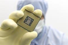 Ein Ingenieur, der in einem klaren Raum tr?gt eine spezielle Uniform und Schutzgl?ser arbeitet, h?lt Prozessor-CPU in den H?nden  lizenzfreies stockbild
