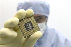 Ein Ingenieur, der in einem klaren Raum tr?gt eine spezielle Uniform und Schutzgl?ser arbeitet, h?lt Prozessor-CPU in der Hand im lizenzfreies stockbild