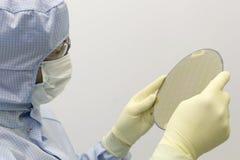 Ein Ingenieur, der in einem klaren Raum tr?gt eine spezielle Uniform und Schutzgl?ser arbeitet, h?lt Siliziumscheibe mit Mikrochi lizenzfreie stockbilder