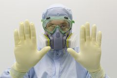 Ein Ingenieur des Labors eine spezielle Uniform und Schutzgl?ser tragend und Gesichtsmaske gegen chemische Giftshow stockbild