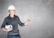 Ein Ingenieur im weißen Sturzhelm, der Pläne hält Lizenzfreie Stockfotografie