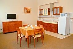 Ein Innenraum der Küche in den warmen Farben mit einem Bild auf einer Wand Lizenzfreies Stockfoto