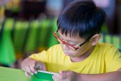 Ein intelligentes Telefonhalten/in der Hand aufpassend von den asiatischen Kindern, die Gläser tragen, die Blaulicht blockieren,  Lizenzfreies Stockbild
