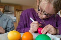 Ein 7-jährige Mädchen malt ein rotes punktiertes Ei für Ostern stockbild